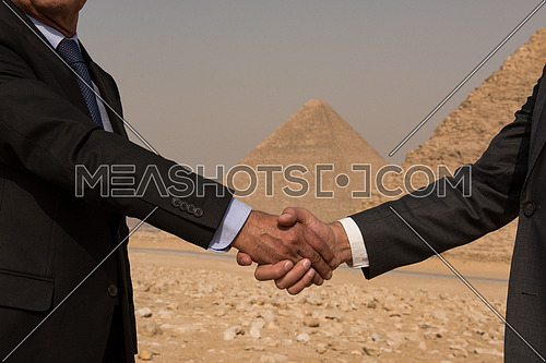 business men hand shake in Egypt by the pyramids