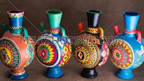 Still life of four decorated colorful handcrafted pottery jugs on sackcloth background, one of the art works of Ebtessam ElGohary, a contemporary Egyptian artist specialized in pottery painting art