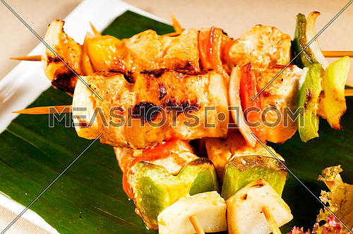 fresh chicken and vegetables skewers on a palm leaf thai style