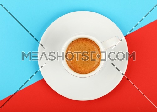 Close up one white cup full of espresso coffee on saucer over colorful red and blue background, elevated top view, directly above