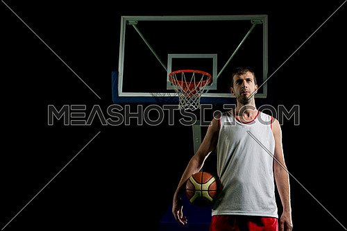 Basketball player portrait  on basketball court holding ball with black isolated background