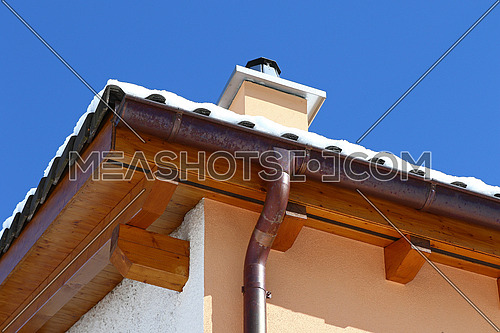 New roof top detail with ceramic tiles, chimney and copper water gutter with snow against blue skies