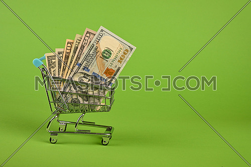 Close up several different value US dollar paper currency banknotes in small shopping cart over green background, low angle side view