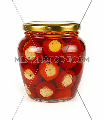Close up of one glass jar of pickled red hot cherry chili pepperoncini peppers stuffed with soft ricotta cheese, with golden lid over white background, low angle side view