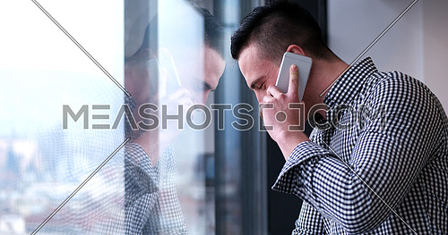 laughing man talking on the phone in office interior