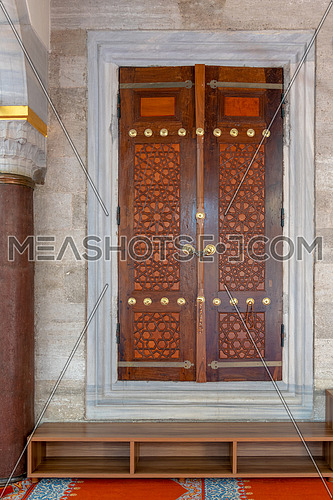 Wooden aged engraved door and marble wall at Suleymaniye public historic mosque, Istanbul, Turkey