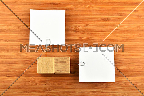 Different Opinion - Two white paper notes with wooden holders in different directions on wooden bamboo background for presentation