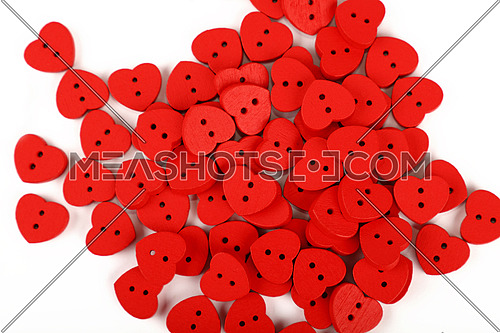 Red heart shaped handmade wooden sewing buttons over white, close up, elevated top view