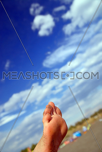 A female foot on the beach with the sky in the background