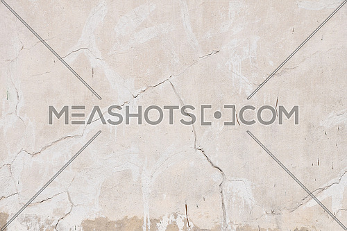 Background texture of old beige pink painted plaster wall with cracks and grunge repair stains