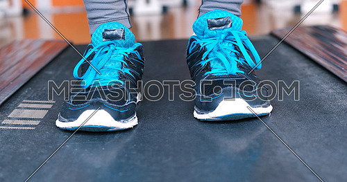 Close up of running black female feet in sneakers in gym