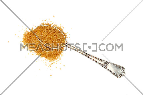 Close up one vintage silver metal spoon full of raw brown cane sugar with pinch spilled and spread around, isolated on white background, elevated top view, directly above
