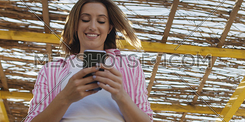 young woman using mobile cell smart phone app at beach during sunset on autumn day