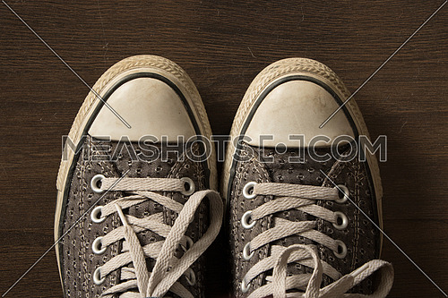 Top shot of a casual pair of shoes white and grey on a woody background