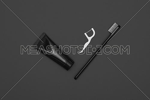Close up one black toothpaste tube, floss and toothbrush over dark grey background, masculine dental care flat lay, elevated top view, directly above