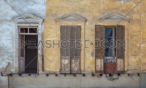 Aged abandoned retro vintage grunge house facade with broken windows and weathered shutters