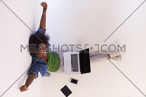 Portrait of happy young african american woman sitting on floor with laptop top view