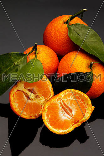 vivid orange tangerine on black reflective surface