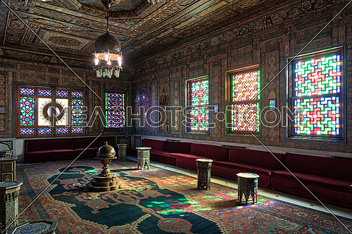 Cairo, Egypt - December 2 2017: Manial Palace of Prince Mohammed Ali. Syrian Hall with ornate wooden wall and ceiling, windows with colored stained glass and Ottoman Empire logo, old ornate chandelier, red couches, tea tables and ornate carpet