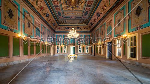 Royal era historic Manasterly Palace with beautiful elegant carved frames on green wall with ornate borders, floral decorated ceiling, chandelier, narrow windows, and marble floor, Cairo, Egypt