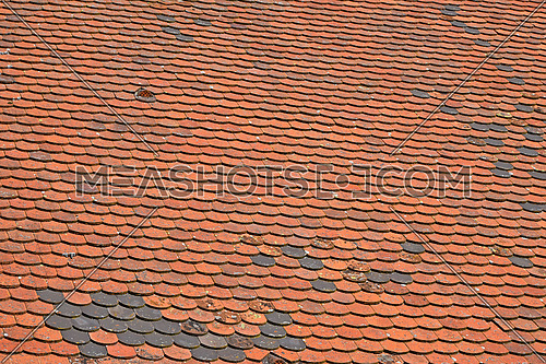 Old weathered vintage traditional red brown ceramic roof tiles pattern background, close up, low angle side view