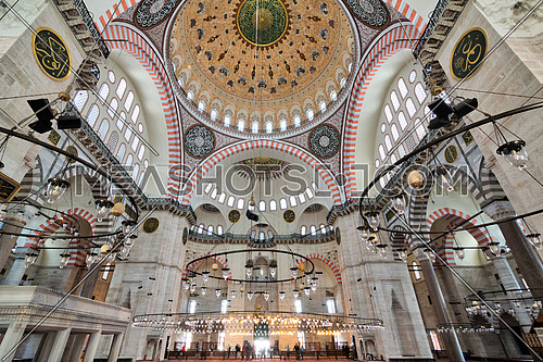 Istanbul, Turkey - April 19, 2017: Interior of Suleymaniye Mosque, with a huge pillars, arches, windows and tourists visiting the mosque, Istanbul, Turkey