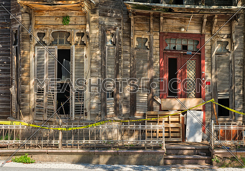 Vintage door and window on abandoned wooden house with small balcony and rusted metal fence on street level