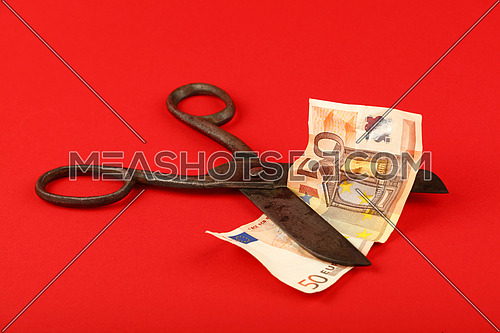 Europe financial crisis, decline of European economy and Euro exchange rate illustrated, old vintage scissors cut fifty EUR banknote on red background