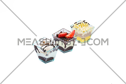 Arranged in a row diagonally,three cupcakes with choccolate,white choccolate, fruits,cream and custard in a plastic cup,isolated on white background.