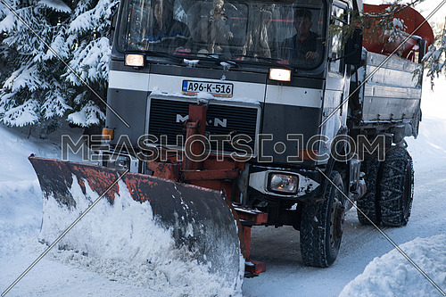 snow truck with plow on winter road cleaning fresh snow