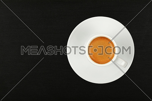Close up one white cup full of espresso coffee on saucer over black chalkboard background, elevated top view, directly above