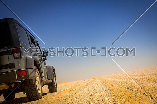 4x4 vechile on an off road track with yellow gravel and a blue sky