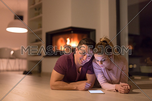 Young Couple on the floor in front of fireplace surfing internet using digital tablet on cold winter night