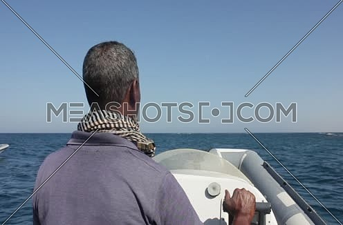 Mid Shot for a male Sailor sail with Motorboat in the Red Sea at Wadi Lahmi at day - 5D