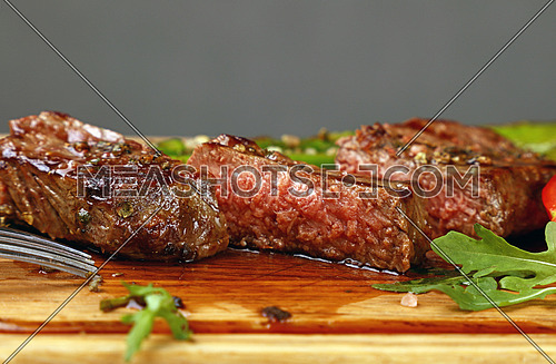 Cut slices of grilled juicy medium cooked beefsteak served on wooden board with fresh green rocket salad, close up, low angle view