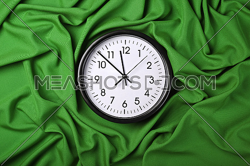 Close up white wall classic clock over green textile background with folded pleats of fabric, elevated top view, directly above