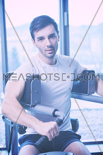 Handsome man running on the treadmill in modern gym