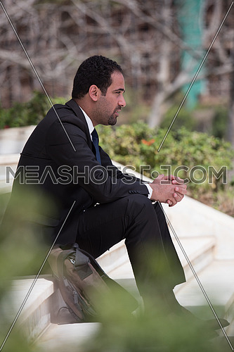 Frustrated business executive sitting on the stairs