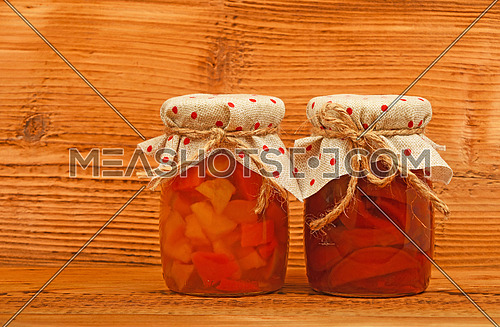Two glass jars of homemade quince jam with textile top decoration at unpainted brown vintage wood