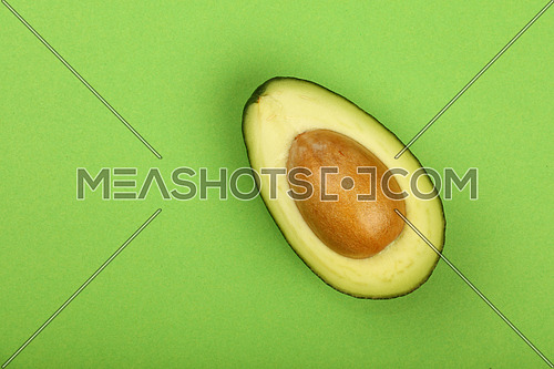 One fresh ripe avocado (Persea gratissima) half with pit stone on green paper background, detail, close up, elevated top view, elevated top view