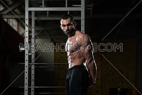 Portrait Of A Young Fit Man Showing Side Triceps Pose - Muscular Athletic Bodybuilder Fitness Model Posing After Exercises