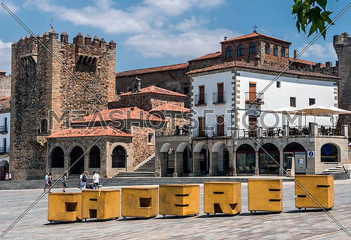 "Caceres, Spain - july 13, 2018: Main square of the city, to the right monument called ""Torre de Bujaco"", Arab building of square plant erected on Roman ashlars, Caceres, Spain"