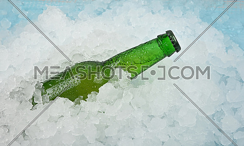 Close up one green glass bottle of cold lager beer on crushed ice at retail display, elevated high angle side view
