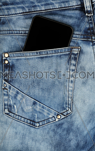 Close up one black smartphone in jeans back pocket, low angle rear view