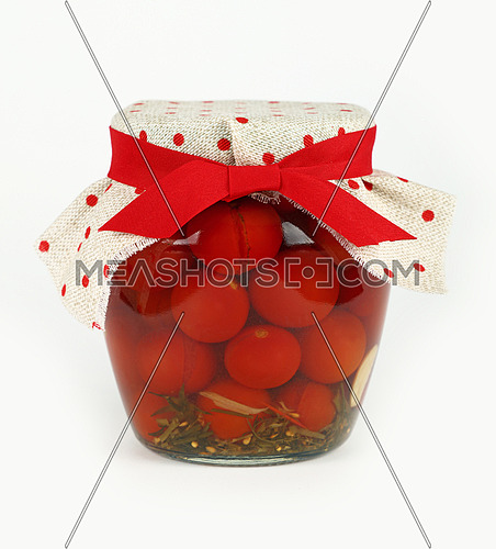 Close up of one glass jar of pickled small red cherry tomatoes with linen canvas lid decoration and red ribbon over white background, low angle side view