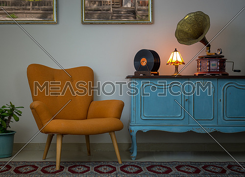 Vintage interior of retro orange armchair, vintage wooden light blue sideboard, old phonograph (gramophone), vinyl records and illuminated table lamp on background of beige wall, and red carpet