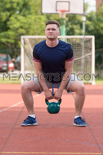 Young Man Working Out With Kettle Bell Exercise Outdoor