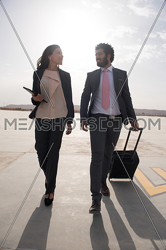 young successful middle eastern business man and woman with a suitcase walking towards airplane