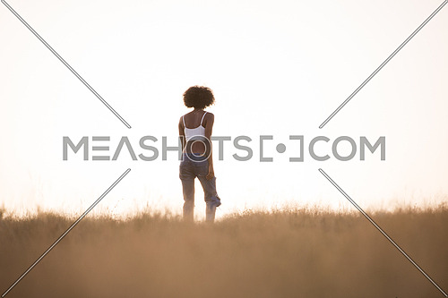 Young beautiful black girl laughs and dances outdoors in a meadow during sunset