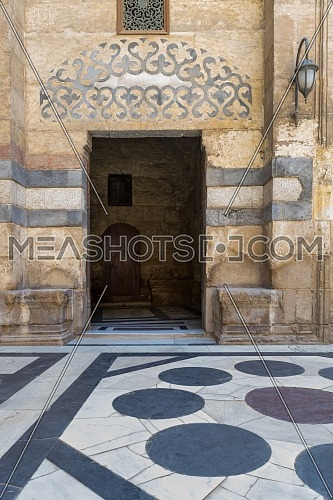 Stone bricks wall and opened door leading to passage at the courtyard of public historic mosque of Sultan Barquq, Moez Street, Old Cairo, Egypt
